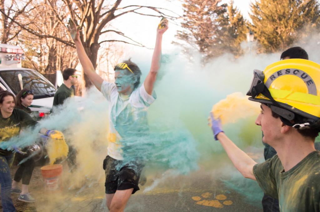 A Color Run participant runs through clouds of powder.